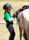 Tightening the Stirrups. A little girl tightening up the stirrups on her pony Stock Photos
