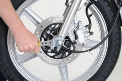 Tightening wheel. Mechanic tightening the wheel nut on a motorcycle Royalty Free Stock Images