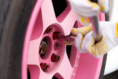 Tightening  wheel nuts. Tightening pink wheel nuts in gloves Royalty Free Stock Images