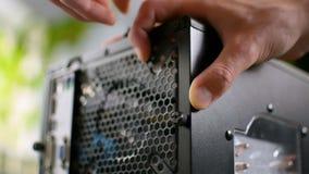 Tighting di montaggio della cassa con computer personale del PC sul primo piano audace della mano del perno della vite video d archivio