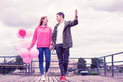 Romantic short-haired guy looking on his girlfriend and carrying her hand. Tightly holding. Romantic short-haired guy looking on his girlfriend and carrying her royalty free stock photography