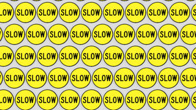 Tightly Packed Arrangement of Yellow Slow Signs Stock Photos