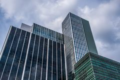 Tightly standing modern glass office buildings against cloudy sky. Tightly standing modern glass office buildings against summer cloudy sky. Shot in the center Royalty Free Stock Photography