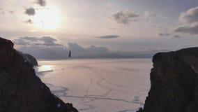 Tightrope walker on the horizon. Slackline training on a high rock. 4K stock video footage