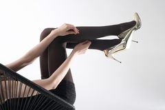 Tights. Shapely female legs in pantyhose and high heels. Female legs in pantyhose and golden high heels Stock Photo