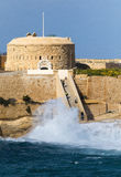 Tigne point, Malta, with waves crashing on the shore Stock Photography