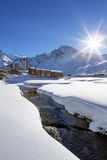 Tignes-Dorf mit Sonne und Nebenfluss Stockbilder