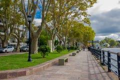 TIGRE, LA ARGENTINA - 2 DE MAYO DE 2016: vista agradable de algunos árboles en el medio de la acera al lado del río delante de Imagen de archivo