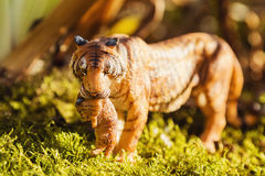 Tigress with cub in teeth. Tiger toy figurine in situation. Royalty Free Stock Photos