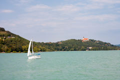 Tihany-Halbinsel mit der Abtei und ein Segelboot angesehen von einem Schiff Lizenzfreies Stockbild