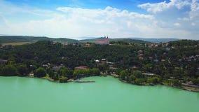 Tihany, Hongarije - 4K luchtlengte van kleurrijk Meer Balaton en haven van Tihany bij dag stock footage