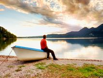 Tiired man in red shirt sit on old fishing paddle boat at mountains lake coast. Stock Photos