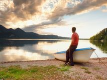 Tiired man in red shirt sit on old fishing paddle boat at mountains lake coast. Royalty Free Stock Photo