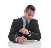 Tijd: aantrekkelijke zakenman die zijn die horloge bekijken op wh wordt geïsoleerd Royalty-vrije Stock Afbeelding