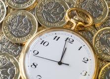 Tijd en geld, een gouden horloge op hoogste Britse pondmuntstukken Stock Foto