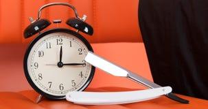 Tijd om een baard, scheermes naast een klok op een oranje achtergrond te scheren stock afbeeldingen