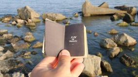 Tijd om idee te reizen, hand die een boek met de inschrijving en rotsen op het overzees houden stock video