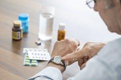 Tijd om pillen voor de oude mens te nemen Stock Foto
