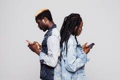 Tijd om telefoons te gebruiken Zijportret die van Afrikaans paar rijtjesholdings mobiele telefoons bevinden zich tegen witte acht stock foto