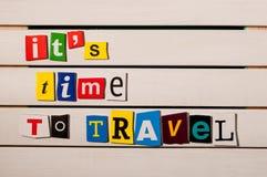 Tijd te reizen - geschreven met de brievenknipsels van het kleurentijdschrift op houten raad Stock Foto's