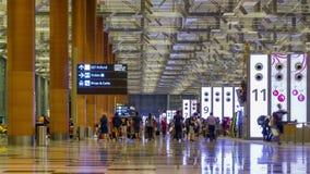 Tijd-tijdspanne: De bezoekers lopen rond Vertrekzaal in Changi Internationale Luchthaven, Singapore