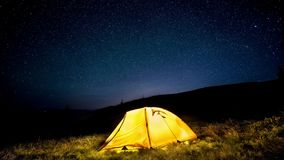 tijd-tijdspanne Gloeiende het kamperen tent in het bos van de nachtberg onder een sterrige hemel stock videobeelden