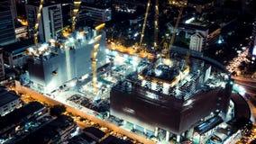 Tijd-tijdspanne van bouwwerf bij nacht met lichte slepen van verkeer in de stad, hoogste mening Geavanceerd bouwtechnologieconcep stock footage