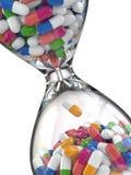 Tijd van geneeskunde Pillen in zandloper Stock Afbeeldingen