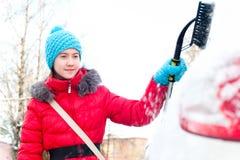 Tijd voor het openlucht werken! Jonge tiener die sneeuwauto schoonmaken Royalty-vrije Stock Foto's