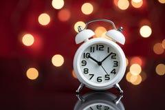 Tijd voor partij en kielzog tot het werk, witte wekker met partij Stock Fotografie