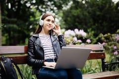 Tijd voor weinig rust Studentenzitting op bank die aan muziek luisteren en laptop met behulp van en hoofdtelefoons in Universitai royalty-vrije stock afbeeldingen