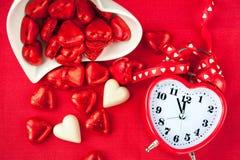 Tijd voor zoete liefde Rode hart gevormde klok met chocolade Royalty-vrije Stock Fotografie