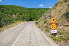 Tijdelijke verkeersteken op wegkant van berg bosweg stock afbeelding