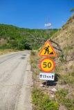 Tijdelijke verkeersteken op wegkant van berg bosweg stock foto's