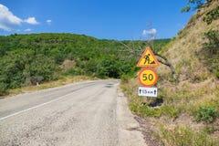 Tijdelijke verkeersteken op wegkant van berg bosweg royalty-vrije stock foto's