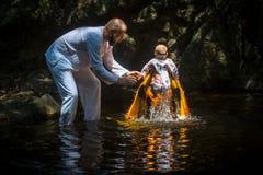 Tijdens de onderdompeling van het ritendoopsel in water - het eerste en belangrijkste Christelijke sacrament Royalty-vrije Stock Foto's