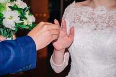 Tijdens de prestaties van de gelofte, zet de bruidegom op de vinger van de bruid een overeenkomsten gouden ring Royalty-vrije Stock Fotografie