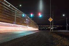 Tijdopnamefoto met een straat bij nacht en automobiel koplampen en verkeerslicht royalty-vrije stock fotografie