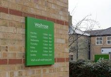 Tijdschema bij de ingang aan een bekende, Britse kleinhandelsketting wordt gezien die stock afbeeldingen
