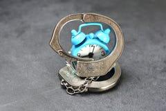 Tijdslaaf of gevangene van het tijdconcept met metaalhandcuffs en wekker op donkere achtergrond stock foto