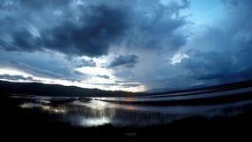 Tijdspanne van de wolken de bewegende tijd over meermening bij zonsondergang met regen en onweersachtergrond in platteland stock video
