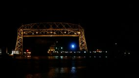 Tijdtijdspanne bij nacht van twee schepen die onder lucht de liftbrug van Duluth gaan