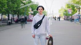 Tijdtijdspanne die van knappe tiener zich buiten in de straat met skateboard bevinden stock footage