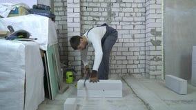 Tijdtijdspanne van bouwer die gelucht concreet blok met handzaag zagen stock footage