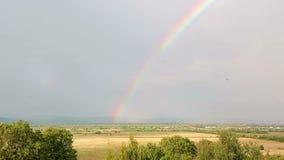 Tijdtijdspanne van een regenboog tegen een berglandschap en een bewolkte en regenachtige hemel stock footage