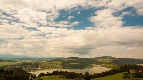 Tijdtijdspanne van het Bewegen van Wolken over een Meer en een Dorp in een Bergvallei stock video