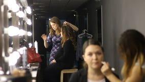 Tijdtijdspanne van het vrouwelijke kappers en van make-upkunstenaars haar van de vestigingscliënt ` s en make-up in schoonheidssa stock video