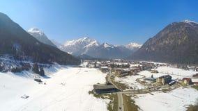 Tijdtijdspanne van kleine Alpiene toevluchtstad bij oever van het meer, reusachtige bergen, sneeuwpieken stock videobeelden