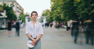 Tijdtijdspanne van meisje in moderne kleding die camera bekijken die zich in stadsstraat bevinden stock video