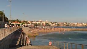 Tijdtijdspanne van overvol zandig strand in Cascais dichtbij Lissabon, Portugal tijdens de zomer Dit strand is genoemd geworden P stock videobeelden